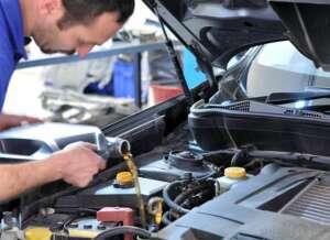 meccanico che versa l'olio nel motore di un auto